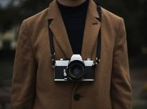 Man in a coat with a vintage film camera royalty free stock photography