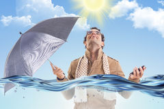 Man in the coat in the water with an umbrella Royalty Free Stock Images