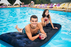 Man with cocktail lying on an inflatable mattress in pool with happy female out of focus next to him Royalty Free Stock Photos