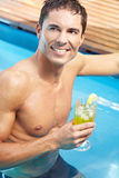 Man with cocktail in pool Stock Photo