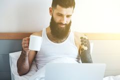 Man with coffee in bed with laptop Stock Image