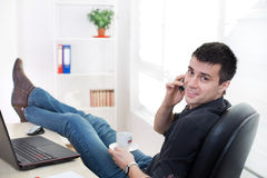 Man on coffee break in the office. Young handsome man sitting at office desk with legs on table, having coffee break and talking on cell phone Royalty Free Stock Photo