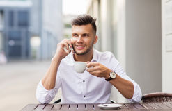 Man with coffee calling on smartphone at city cafe Royalty Free Stock Images