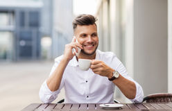 Man with coffee calling on smartphone at city cafe. Business, technology, communication and people concept - smiling young man drinking coffee and calling on royalty free stock image