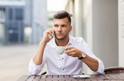 Man with coffee calling on smartphone at city cafe Stock Photo