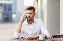 Man with coffee calling on smartphone at city cafe Royalty Free Stock Photos