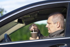 Man with coffee in the car Royalty Free Stock Image