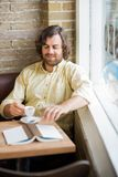 Man With Coffee Cup And Book In Cafeteria Stock Photo