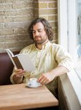Man With Coffee Cup Reading Book In Cafe Royalty Free Stock Image