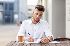 Man with coffee and folder writing at city cafe. Business, education and people concept - young man with coffee and folder writing at city street cafe royalty free stock photography