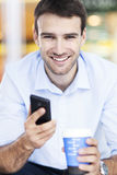 Man with coffee and mobile phone Stock Photos