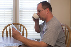 Man with Coffee and Newspaper Stock Photos