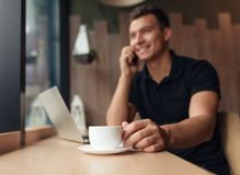 Man in coffee shop having drink and speaking on phone. Closeup of man with white cup of hot drink sitting at table in coffee shop chatting via phone in daylight stock image