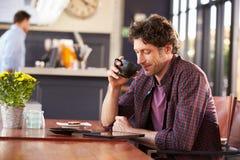 Man at coffee shop, reading digital tablet Royalty Free Stock Photo