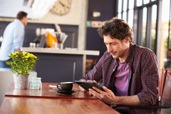 Man at coffee shop, using digital tablet Royalty Free Stock Image