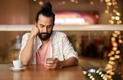 Man with coffee and smartphone at restaurant stock image
