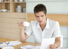 Man With Coffee and Working on Finances. Portrait of young man working on his home finances in the kitchen Royalty Free Stock Photography