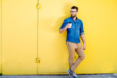 Man with coffee on the yellow background Stock Photos