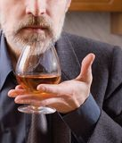 Man with a cognac glass. Man's hand holding a glass of classy brandy Royalty Free Stock Photo