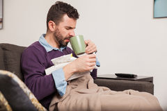Man with a cold drinking some tea. Profile view of a young handsome man drinking some tea to ease the symptoms of the flue stock photo