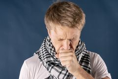 Man with cold and flu illness suffering from a headache and cough. Blue background stock photography