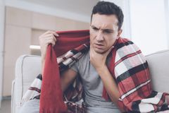 A man with a cold sits on the couch, hiding behind a red rug. He has a sore throat Royalty Free Stock Image