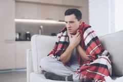 A man with a cold sits on the couch, hiding behind a red rug. He has a sore throat Royalty Free Stock Photography