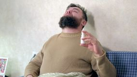 A man with a cold sits on the couch. He sprinkles a special nasal spray into his nose. 4k stock video footage