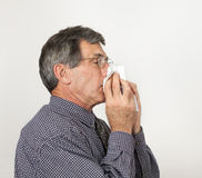 Man With Cold Sneezing. Man with bad cold or flu sneezing into handkerchief Stock Images