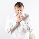 Man with cold. Sneezing into paper towel Royalty Free Stock Image