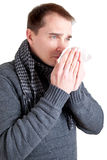Man with cold sneezing into a tissue Stock Photos