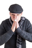 Man with cold sneezing into a tissue Royalty Free Stock Photos