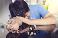 Man collapsed after a overdose. Of drugs, Tablet drugs. In-hand with a syringe Stock Photography