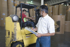 Man With Colleague In Forklift Track At Factory Royalty Free Stock Photo