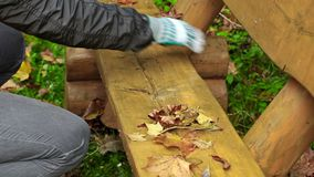 Man collect leaves from the bench in the park stock footage
