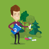Man collecting garbage in forest. Royalty Free Stock Images