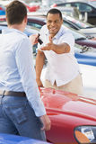Man collecting new car from salesman. On lot Stock Photo