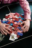 Man collecting pile of gambling chips on table, mid section, elevated view Stock Images
