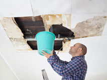 Man Collecting Water In Bucket From Ceiling Stock Images