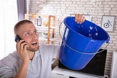 Man Collecting Water Leakage In Bucket While Calling Plumber. Young Man Collecting Water Leakage In Bucket While Calling Plumber On Smartphone stock photos