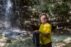 The man collects a backpack near a mountain river and waterfall Stock Image