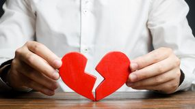 A man collects a broken heart in his hands. Concept of love and relationships. Family psychotherapist services. Reconciliation. Saving the family. Search for stock photos
