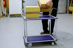 Man collects cardboard boxes. To material handling trolley in warehouse stock photo