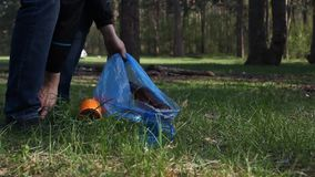 A man collects garbage in the forest in a package. Collect garbage stock video footage