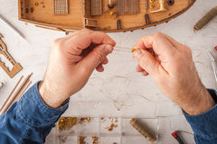 Man collects ship model on a white table Royalty Free Stock Image