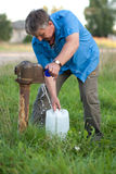 A man collects the water from Royalty Free Stock Image