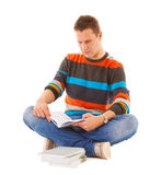 Man college student sitting and reading book studying for exam. Isolated. Studio shot Stock Image