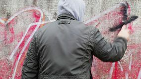 Man with color spray can near the old wall stock footage