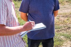 A man in a colored shirt with a notebook in his hands writes with a pen, discusses with another person. In the field in the summer agronomist royalty free stock photography