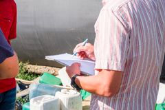 A man in a colored shirt with a notebook in his hands writes with a pen, discusses with another person. In the field in the summer agronomist stock photography